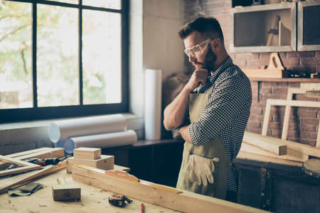 Pensive hardworking thoughtful serious concentrated minded cabinet-maker standing near table with instruments and thinking over new diy