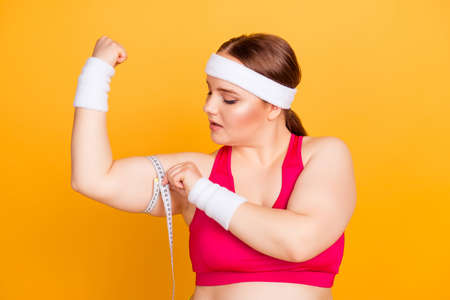 Close up portrait of confident concentrated sportive fatty woman wearing pink top and sweat-band, she is measuring her upper arm using tape measure Archivio Fotografico