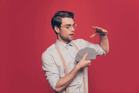 Professional, cunning magician, illusionist, gambler in casual outfit, glasses, holding set deck of cards, making performance, show trick standing over red background