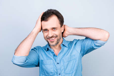 Close up portrait of attractive handsome cheerful excited satisfied glad brunette man with toothy beaming smile checking haircut in mirror after visiting barbershop isolated on gray background Reklamní fotografie