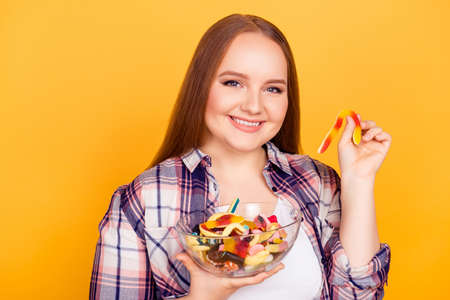 I cant deny myself such tasty gummy candies! Close up portrait of cheerful joyful excited lady holding a plate full of jelly babies in one hand and gummy worm in another isolated on yellow background