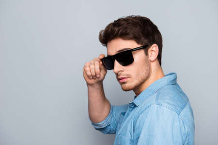 Portrait with copy space of concentrated, trendy, half-turned, cool, handsome guy in black glasses, jeans shirt