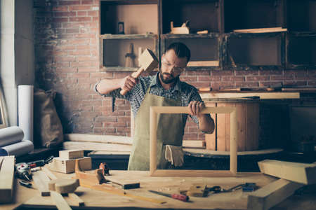 Concentrated successful knowledgeable smart bearded craftsman wearing checkered shirt apron and safety goggles is repairing a wooden frame for photo and hitting with a chisel Stock Photo
