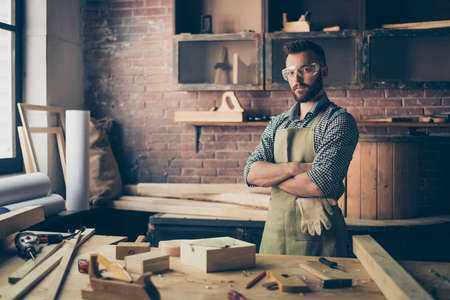 Serious concentrated confident qualified handsome bearded cabinet-maker wearing apron and safety glasses is standing with crossed arms in his workshop Banco de Imagens