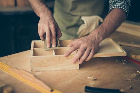 手作りの木箱の表面を研磨紙でサンドする手工芸士の手のクロップド写真をクローズアップ
