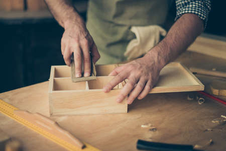 Close up cropped photo of handicraftsmans hands sanding the surface of handmade wooden box with abrasive paper