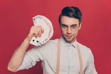 Professional, cunning magician, illusionist, gambler in casual outfit, glasses, holding, showing set deck of card near face, standing over red background