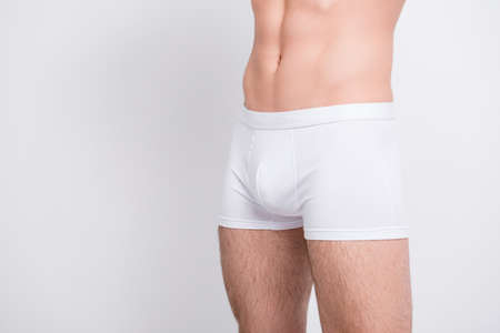 Cropped close up photo of mans strong muscular legs wearing white classic boxer-shorts isolated on gray background copy-space cutout Banco de Imagens