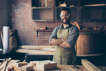 Satisfied cheerful joyful smiling with stylish hairdo bearded wearing apron woodmaster is standing near desktop with crossed arms in his workshop, workstation Banco de Imagens