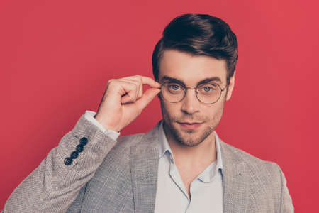 Close up portrait of clever, smart, unshaved manly, stunning guy in glasses holding eyelet of spectacles on his face, looking at camera, isolated on red background