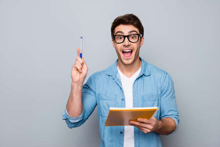 Handsome, attractive, glad, positive, funny guy in glasses with wide open mouth finally found a solution how to make exercise, having raised pen and notebook in hands