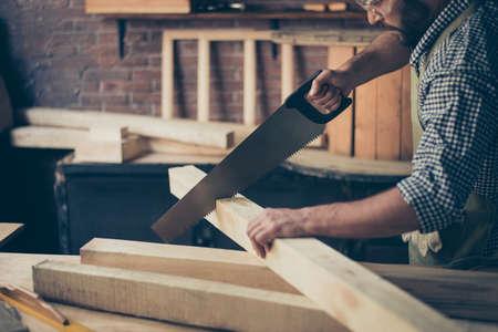 Bijgesneden close-up foto van geconcentreerde serieuze professionele hardwerkende gekwalificeerde schrijnwerker die een houten plank op zijn bureaublad zag met een handzaag Stockfoto