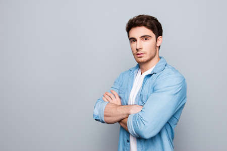 Portrait with copy space, empty place of stunning, brutal, sexy, concentrated, cool man in jeans shirt having his arms crossed, looking at camera Stock Photo