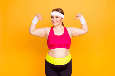 Happy cheerful positive excited fatty woman, stretch marks cellulite pointing on herself with thumbs-up isolated on vivid yellow background Stock Photo - 97561335