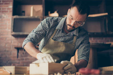 Handsome gifted hardworking confident concentrated bearded handyman clothed in checkered shirt apron gloves and safety glasses is sanding a little wooden casket with emery paper, working in a garage Stock Photo