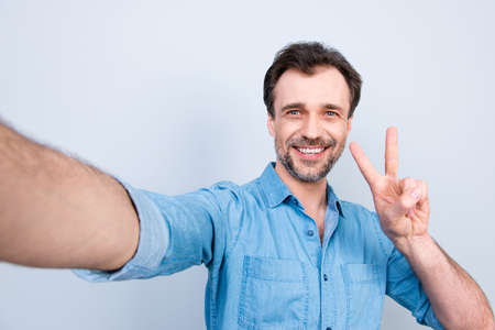 Close up portrait of joyful glad friendly bearded with beaming smile guy showing peace symbol taking selfie isolated on gray background Reklamní fotografie