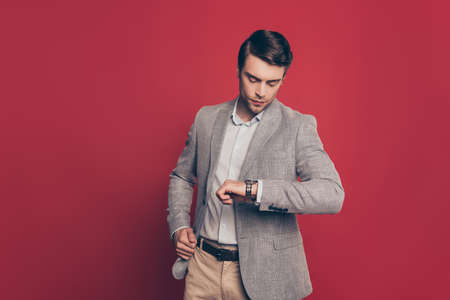 Portrait of punctual, virile, harsh, stunning financier looking at his watch on arm, nervous that his partner is late, isolated on red background, checking time Stock Photo