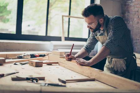 Seitenprofilansichtfoto des fleißigen beschäftigten professionellen überzeugten Tischlers, der Maß der hölzernen Planke mit einem Bleistift nahe anderen Instrumenten misst