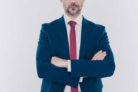 Cropped close up photo of serious concentrated confident wearing dark blue jacket with red tie standing with folded arms isolated on gray background