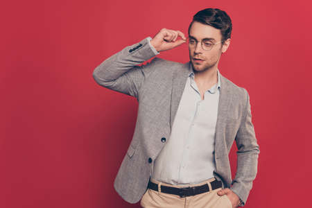 Portrait of stunning, virile, harsh, modern man holding hand in pocket of pants and eyelet of glasses on his face, looking to the side, standing over red background Stock Photo