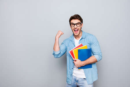 Portrait with copy space of cheerful, joyful, attractive guy with stubble having three colorful copybooks in arm, celebrating passed exams, graduation, isolated on grey background Zdjęcie Seryjne
