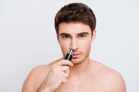 Close up portrait of handsome confident concentrated with bristle stubble man using electric machine for getting rid of unnecessary hair in nose isolated on gray background Stock Photo