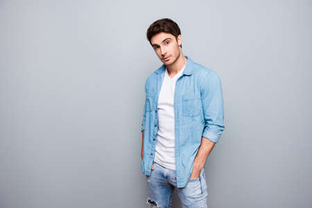 Manly, masculine man in jeans outfit, holding hands in pockets of pants, looking at camera, standing over gray background Stok Fotoğraf