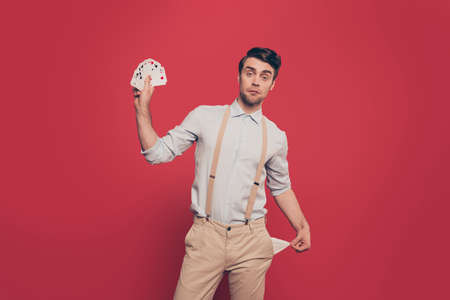Professional, cunning magician, illusionist, gambler in casual outfit, holding, showing set of cards and empty pocket out, standing over red background Stock fotó