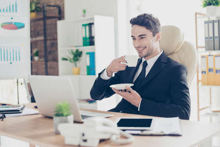 handsome attractive smart employee sitting on luxurious armchair drinking aromatic tea in the morning reading news on the internet