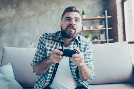 Excited cheerful nervous handsome joyful bearded guy wearing checkered shirt and white tshirt is playing videogames at home, sitting on sofa