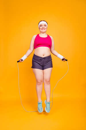 Full-size full-length photo of cheerful female obese athlete with stretch-marks wearing pink top, shorts and sneakers