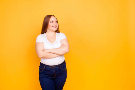 Feliz alegre alegre confiado con cara gordita mujer de gran tamaño con camiseta casual y jeans azul oscuro, de pie con los brazos cruzados, mirando el espacio en blanco vacío Foto de archivo