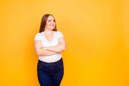 Gelukkig vrolijk blij zelfverzekerd met mollig gezicht oversized vrouw, gekleed in casual t-shirt en donkerblauwe jeans, staande met gevouwen armen, kijkend naar lege lege ruimte Stockfoto - 97560069