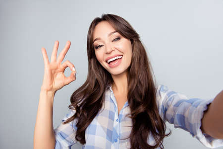 Close up picture of pretty, attractive, nice, cute woman with beaming smile shooting selfie, gesturing ok sign with fingers, having video call, standing over grey background