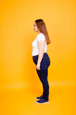 Profile side-view half-faced photo of fatty confident young lady dressed in white tshirt and dark blue jeans, isolated on bright yellow background 스톡 콘텐츠