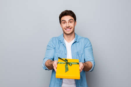 Portrait of cheerful, positive, smiling guy in jeans shirt giving yellow packed box with green bow front to the camera, prepare present for womans day Stock Photo