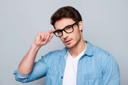 Portrait of stunning, brutal, sexy, concentrated, cool man in jeans shirt holding eyelet of glasses on his face with fingers, looking at camera, isolated on grey background Archivio Fotografico