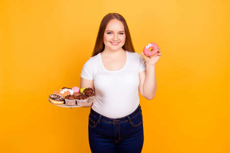 Concept of having dependency on fast unhealthy products. Excited smiling woman she is holding a plate with confectionery and showing funny glazed with frosting donut Stock Photo