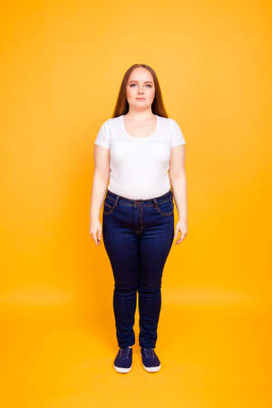Full-size full-length front view portrait of confident concentrated pretty plump woman wearing white tshirt and jeans, isolated on bright yellow background 版權商用圖片