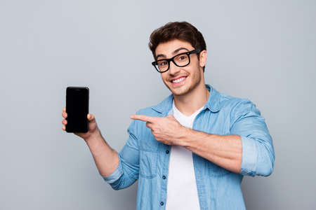 Portrait of cheerful, positive, attractive guy with stubble in jeans shirt, having smart phone with black screen in hand, pointing with forefinger to product