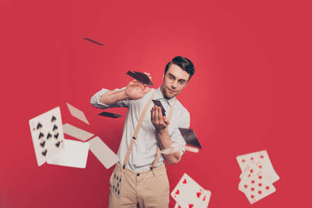 Professional, cunning magician, illusionist, gambler in casual outfit, glasses, throwing, sending cards to the camera, standing over red background Foto de archivo
