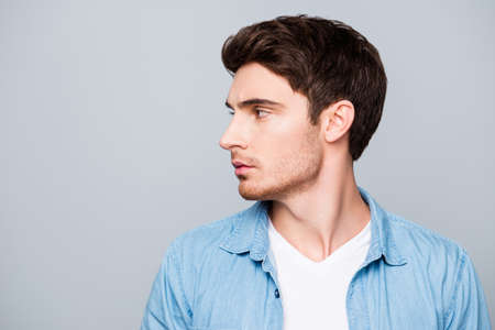 Advertisement concept, side view half face profile with copy space of perfect, attractive man in casual outfit standing over gray background Фото со стока