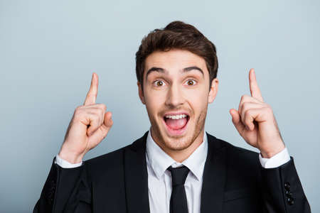 Impressed, astonished, attractive, cheerful, funny guy in black formal wear indicate two forefingers up with wide open mouth and eyes over gray background Reklamní fotografie