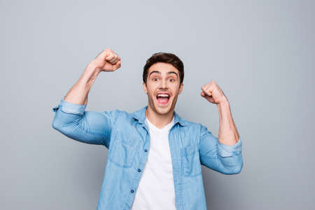 Portrait of lucky, attractive, excited, glad man with wide open mouth and raised arms looking at camera celebrating successfully passed exams
