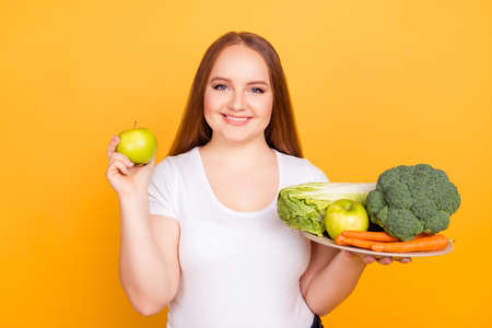 Beautiful energetic cheerful fatty woman wearing white tshirt is holding a plate with fresh vegetables and an apple, isolated on bright yellow background