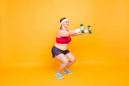 Cute positive cheerful fatty woman is doing deep squats with little green dumbbells, isolated on bright yellow background, copy-space Stock Photo