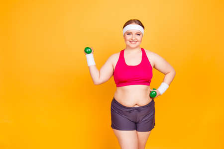 Happy joyful confident with toothy smile girl dressed in sportive outfit is lifting up green little dumbbells and training her arms