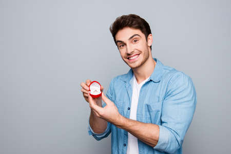 Portrait of cheerful, romantic, smiling guy in jeans shirt with gold ring for his girlfriend, future wife