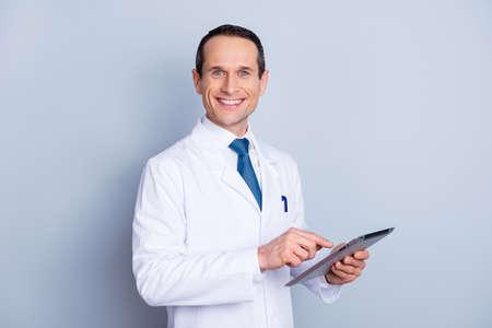Porträt von nettem frohem begabtem intelligentem mit toothy Lächelndoktor, der die moderne Auflage bei der Arbeit lokalisiert auf grauem Hintergrundkopieraum verwendet