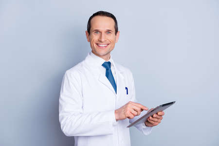 Portrait of cheerful glad gifted smart with toothy smile doctor using modern pad at work isolated on gray background copy-space Stockfoto